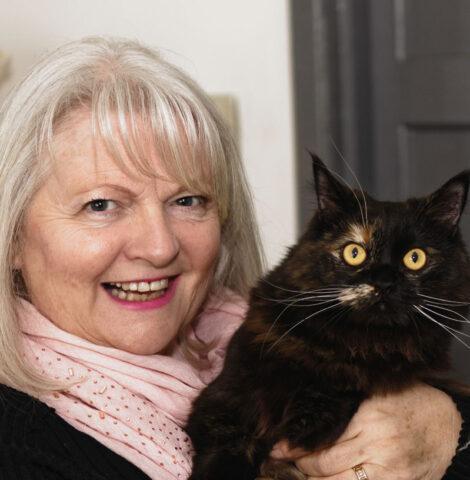Elderly lady holding black cat